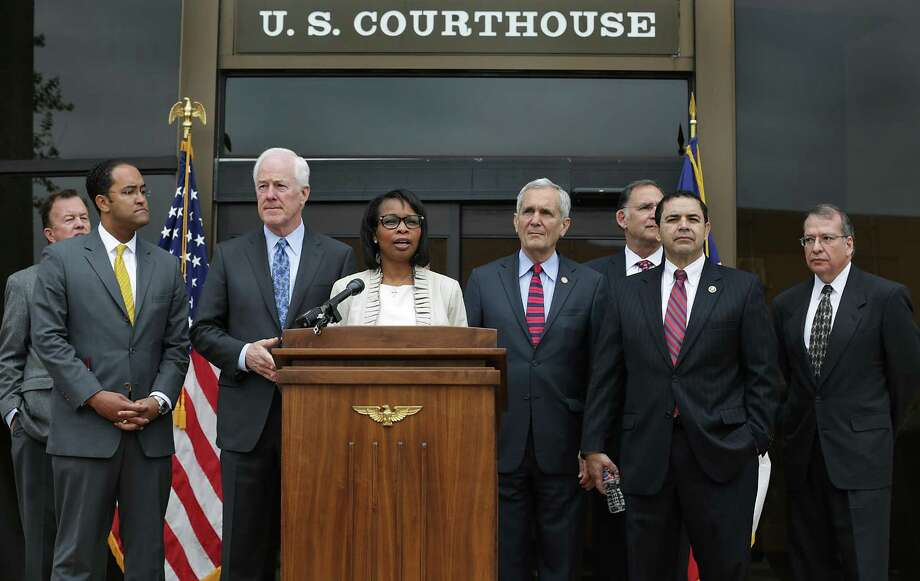 Then-San Antonio Mayor Ivy Taylor speaks to the media in November 2015 after a tour of the John H. Wood Federal Courthouse. Left to right are then-Councilman Joe Krier, Congressman Will Hurd, Sen. John Cornyn, Congressman Lloyd Doggett, Sen. John Boozman, Congressman Henry Cuellar and U.S. Judge Xavier Rodriguez. The districts of Hurd, Doggett and Cuellar could be redrawn as a result of a redistricting trial held in San Antonio recently. Photo: BOB OWEN /San Antonio Express-News / San Antonio Express-News