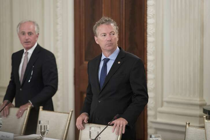 Senator Rand Paul, a Republican from Kentucky, right, and Senator Bob Corker, a Republican from Tennessee, stand next to seats before the start of a lunch with U.S. President Donald Trump, not pictured, and members of Congress at the State Dining Room of the White House in Washington, D.C., U.S., on Wednesday, July 19, 2017. Trump told Senate Republicans Wednesday they should stay in Washington until they repeal Obamacare, two days after GOP efforts to enact a new health-care law collapsed. Photographer: Michael Reynolds/Pool via Bloomberg