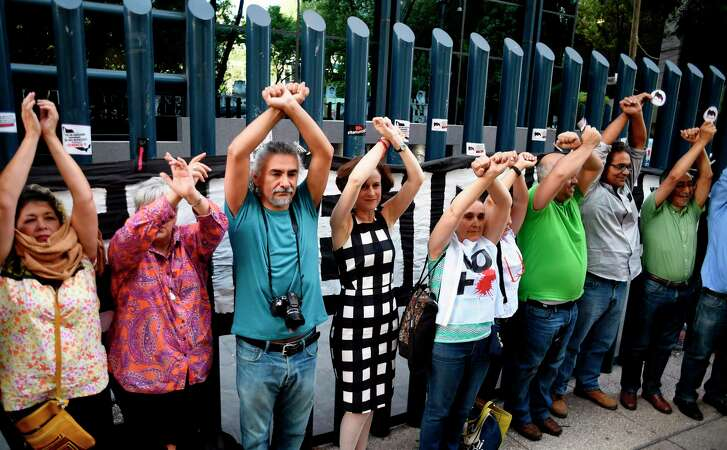 Civil society activists and journalists pretend to turn themselves in during a protest against alleged government spying on the media and human rights defenders, outside the attorney general's office in Mexico City last month.  Mexican prosecutors said Wednesday they have opened an investigation into allegations the government spied on leading journalists, human rights activists and anti-corruption campaigners. (Alfredo Estrella/AFP/Getty Images)