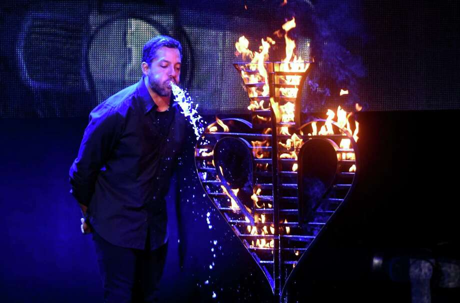 Magician David Blaine puts out a fire by spraying out the copious amount of water that he drank at the Majestic Theatre on Wednesday, July 18, 2017. Blaine set the fire by drinking and spraying kerosene on top of the water. Blaine is on a 50-city tour. Photo: Billy Calzada, Staff / San Antonio Express-News / San Antonio Express-News