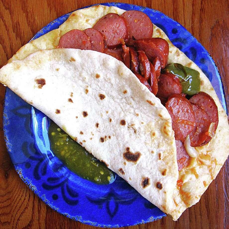 Sausage ranchero taco on a handmade flour tortilla from AV's Food To Go. Photo: Mike Sutter /San Antonio Express-News