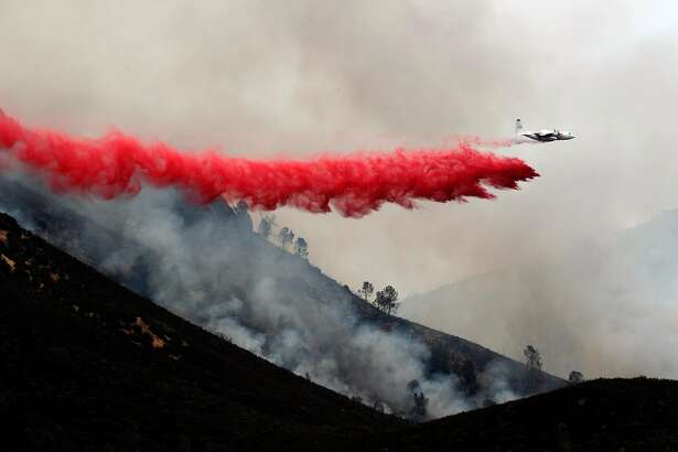 Air tanker drops fire retardant along the ridge line above Lake McClure, as the northern end of the Detwiler fire moves closer to Coulterville, Ca., on Thursday July 20, 2017.