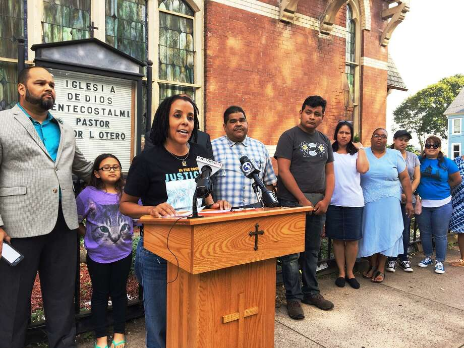 Activist Kica Matos addresses press conference outside church where Nury Chavarria has taken up sanctuary. Pastor Hector Otero is at left. Next to him is Hayley Chavarria, 9, Nury's daughter. Photo: Mary O'Leary / Hearst Connecticut Media