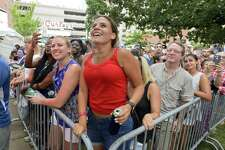 Theresa Elroy, of Stratford, center, and friends jump as the band Sugar Ray performs during the Alive@Five concert.