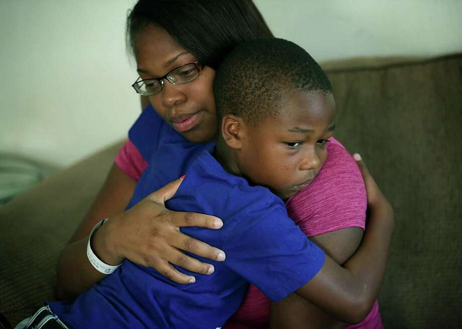 Cyntwanisha Whitley, mother of four year-old De'Earlvion Whitley who was killed in a drive by shooting, is comforted by De'Earlvion's friend Charles Dixon, 6, as family members and friends gather to support each other on Thursday, July 20, 2017. Photo: Bob Owen, Staff / San Antonio Express-News / ©2017 San Antonio Express-News