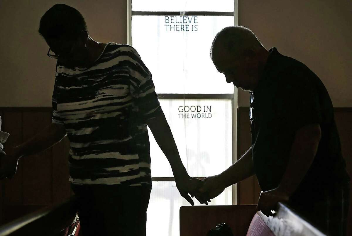 Armond Hathaway, right, and Willie Mae Taylor hold hands during a prayer at Corner Gate Christian Church following a news conference on July 20, 2017, concerning the drive-by shooting death of 4-year-old De-Earlvion Whitley, on July 20, 2017.
