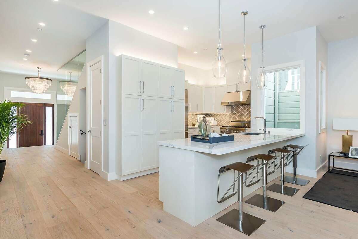 The kitchen enjoys a bar island and pendant lights, as well as ambient lighting above the Shaker cabinetry.