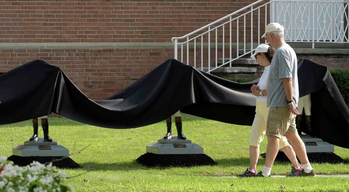 FILE - Pedestrians check out the black drapes put on a new exhibit of lawn jockeys at the National Museum of Racing and Hall of Fame Thursday July 20, 2017 in Springs, N.Y. (Skip Dickstein/Times Union)