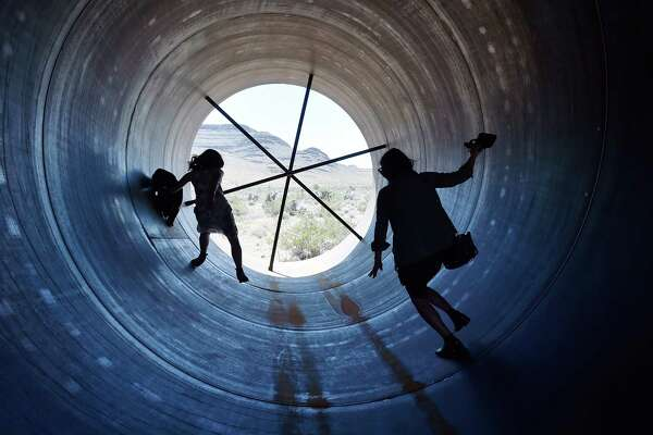 People walk through a tube at the Las Vegas site where Hyperloop One is gearing up to test entrepreneur Elon Musk's hyperloop transportation concept.
