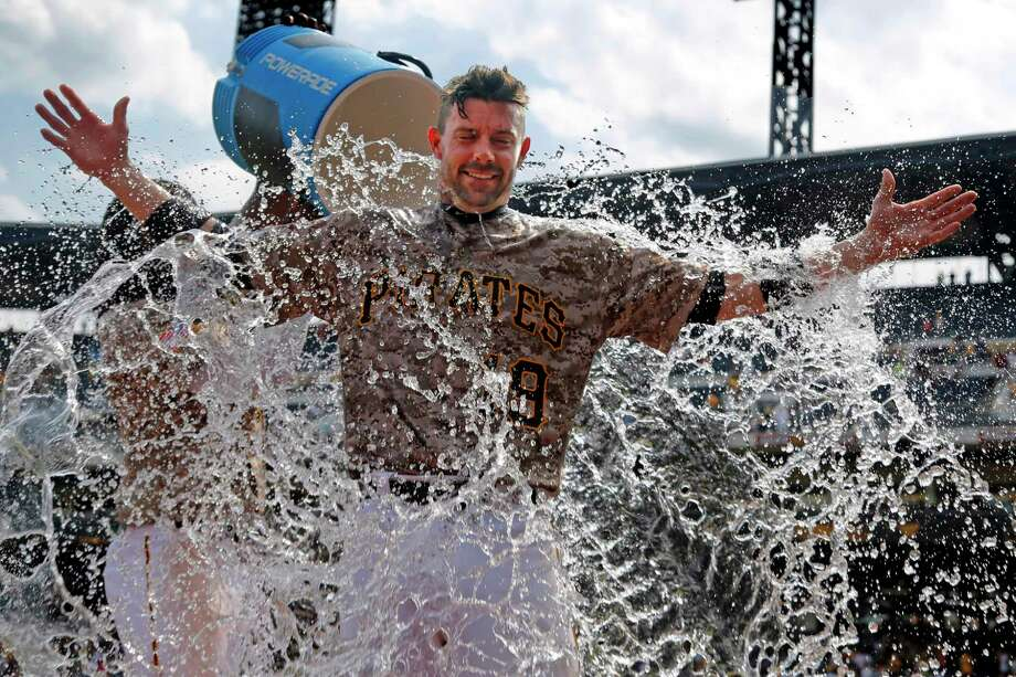 Pittsburgh Pirates' Chris Stewart gets doused by Josh Bell as he waits to be interviewed after a 4-2 Pirates win over the Milwaukee Brewers in a baseball game in Pittsburgh, Thursday, July 20, 2017. (AP Photo/Gene J. Puskar) ORG XMIT: PAGP109 Photo: Gene J. Puskar / Copyright 2017 The Associated Press. All rights reserved.