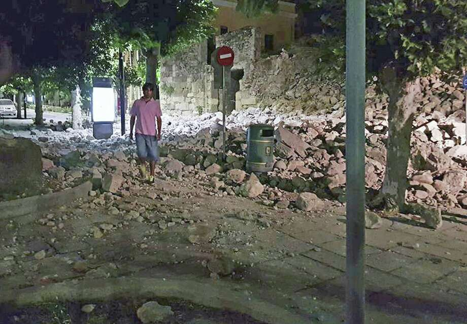 A man walks near a damaged building after an earthquake on the Greek island of Kos early Friday, July 21, 2017. A powerful earthquake struck Greek islands and Turkey's Aegean coast early Friday morning, damaging buildings and a port and killing people, authorities said. (Kalymnos-news.gr via AP) Photo: Associated Press / Associated Press / Kalymnos-news.gr
