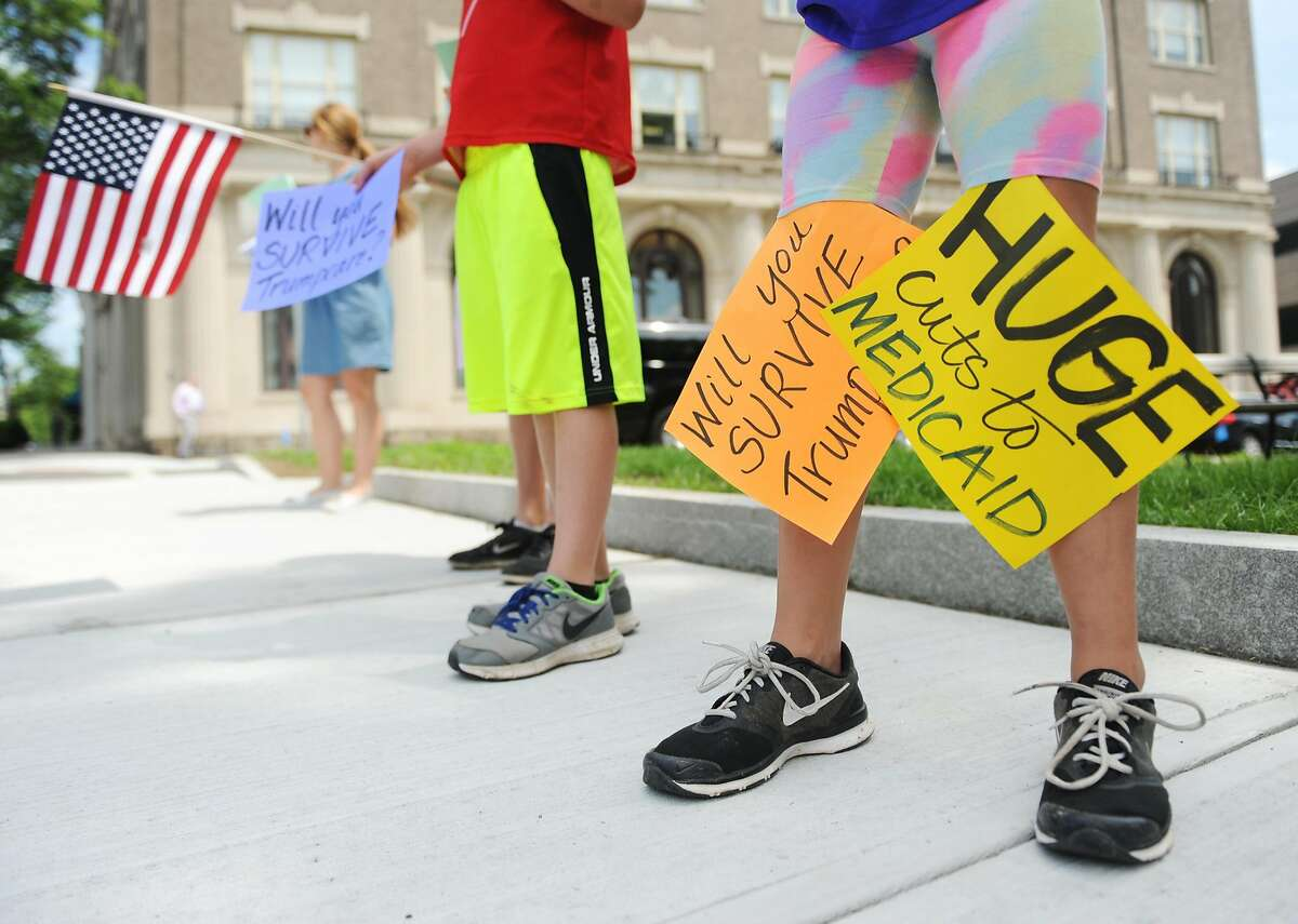 Riverside's Kennedy Fahey, 8, tapes signs to her legs during the anti-Trump group Indivisible Greenwich's protest against the new proposed American Health Care Act outside the Senior Center in downtown Greenwich, Conn. Tuesday, June 27, 2017. The group gave fact sheets about the new proposed healthcare and urged passersby to call their Senators. Facing opposition from both parties, Senate Majority Leader Mitch McConnell announced Tuesday he would delay consideration of the bill until after the Senate's weeklong July 4 recess.