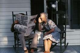 1970s SENIOR COUPLE SITTING ON PORCH ROCKING CHAIRS MAN READING NEWSPAPER WOMAN SHOUTING AT HIM  (Photo by D. Corson/ClassicStock/Getty Images)