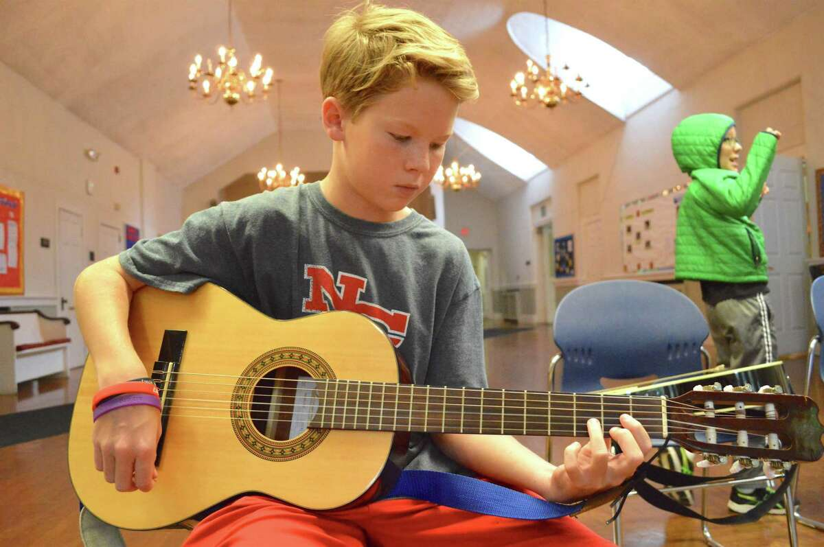 Logan Hickey, 11, of New Canaan, plays a D chord at the Rock Out Summer Camp, held at First Congregational Church of Darien through the Parks & Recreation Department, Friday, July 14, 2017, in Darien, Conn.