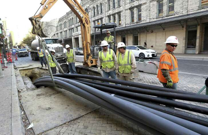 A construction crew lays out utility conduit pipes on West Commerce Street. The construction, mining and natural resources sector in San Antonio  added 1,100 jobs last month.