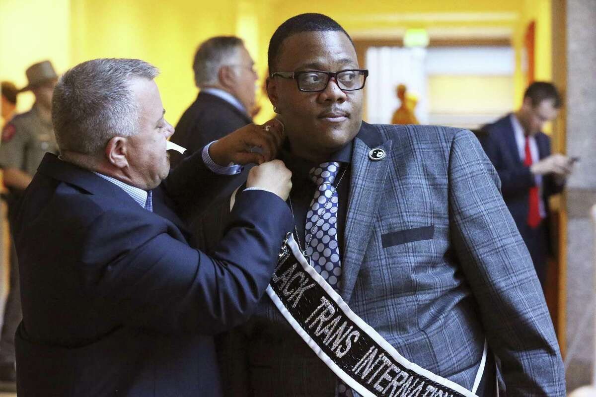 Trenton Johnson gets his Black Trans International sash pinned on by Finnigan Johnson as the Senate State Affairs committee holds a hearing on the bathroom bills filed by Sen. Lois Kolkhorts on July 21, 2017.