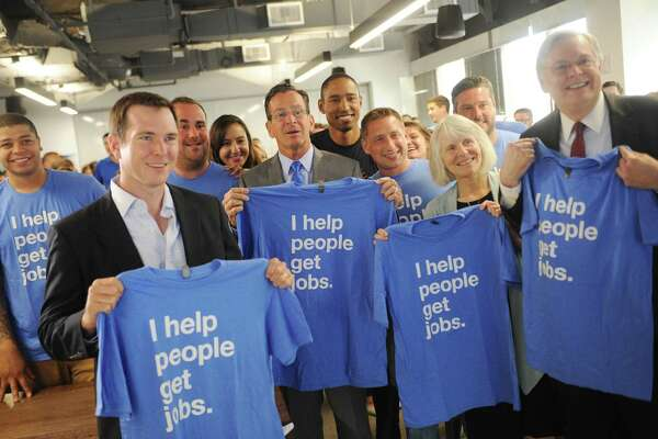 Front row, from left, Indeed SVP and CFO Dave O'Neill, Connecticut Gov. Dannel P. Malloy, Connecticut Department of Economic and Community Development Commissioner Catherine Smith, and Stamford mayor David Martin hold up company T-shirts with employees after speaking at the Indeed headquarters in Stamford, Conn. Wednesday, July 12, 2017. Online job-search giant Indeed plans to create up to 500 new jobs over the next few years through tens of millions of dollars in company investment and state aid, Gov. Dannel P. Malloy and company executives announced Wednesday.