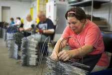 Karen Funk checks metal hangers for quality control as part of her job at the Arnold Center on Thursday. The Arnold Center provides services and support to people with disabilities and/or other unique needs.