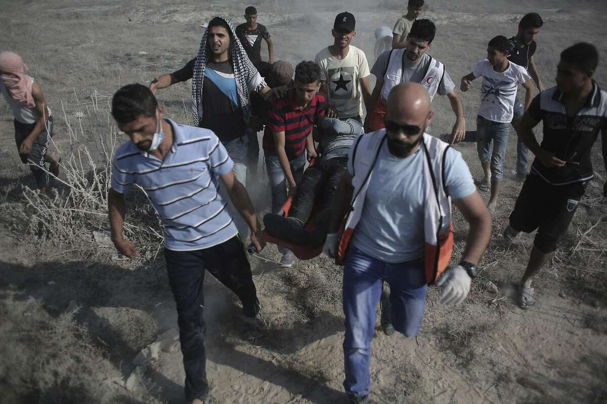 Palestinian medics and protesters evacuate an injured man during clashes with Israeli soldiers on the Israeli border with Gaza, Friday, July 21, 2017. An escalating dispute over metal detectors at a contested Jerusalem shrine turned violent on Friday, setting off widespread clashes between Palestinian stone-throwers and Israeli troops. (AP Photo/ Khalil Hamra)