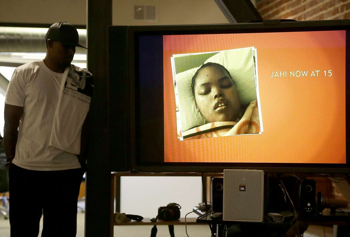 A recent photo of Jahi McMath is shown on a video screen next to her uncle Timothy Whisenton at a news conference in San Francisco, Wednesday, Dec. 23, 2015. McMath's mother Nailah Winkfield's two-year quest to have McMath, who was declared brain dead after complications of a tonsillectomy in 2013, declared legally alive is moving to federal court after attempts to secure an order from a state judge ended in failure. (AP Photo/Jeff Chiu)
