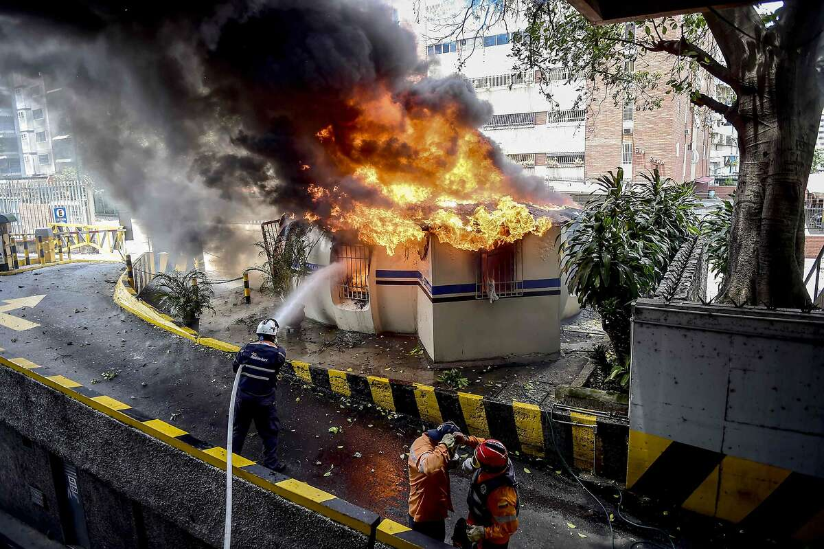 TOPSHOT - Firefighters work to douse the fire on a police boot set ablaze by opposition demonstrators clashing with riot police during an anti-government protest in Caracas, on July 20, 2017. A 24-hour nationwide strike got underway in Venezuela Thursday, in a bid by the opposition to increase pressure on beleaguered leftist President Nicolas Maduro following four months of deadly street demonstrations. / AFP PHOTO / RONALDO SCHEMIDTRONALDO SCHEMIDT/AFP/Getty Images