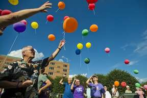 James Peters of Midland, a cancer survivor, left, releases his balloon along with dozens of others during the annual Cancer Services of Midland balloon release on Thursday near The H Hotel.