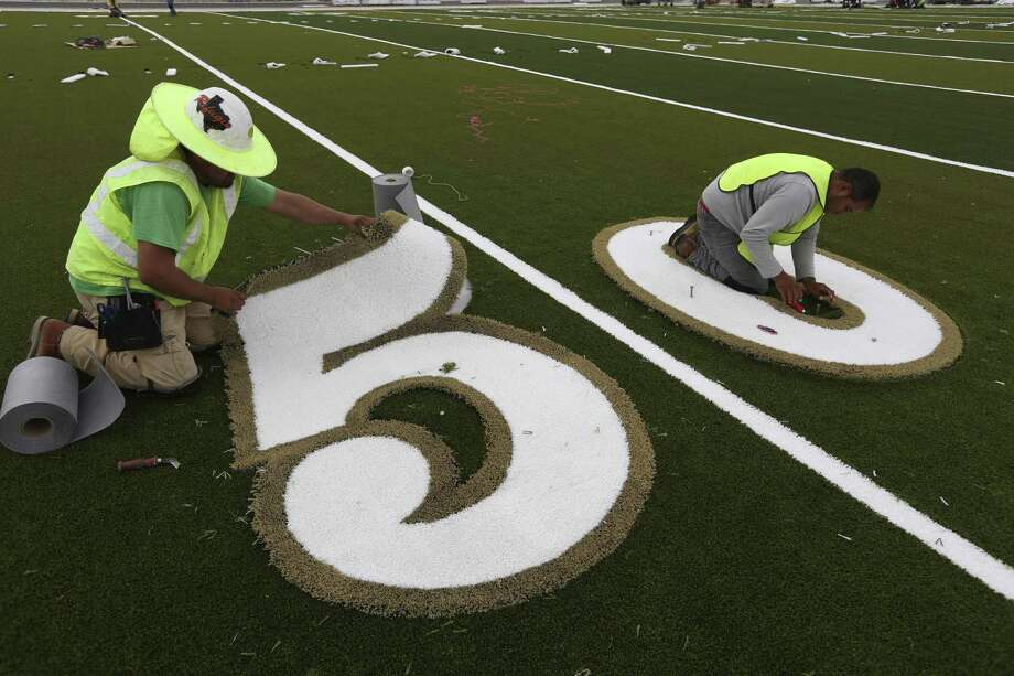 Workers install the numbers on June 29, 2017 at the new Cole High School football field. The field, designed and produced by AstroTurf, is the first of its kind to be installed in Texas. Among other improvements the traditional rubber pellets used in most artificial turf fields are replaced with an organic product the company is calling ZeoFill that helps reduce the turf's surface temperature. Photo: William Luther /San Antonio Express-News / © 2017 San Antonio Express-News