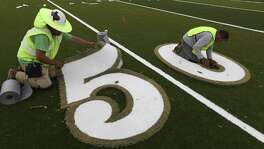 Workers install the numbers on June 29, 2017 at the new Cole High School football field. The field, designed and produced by AstroTurf, is the first of its kind to be installed in Texas. Among other improvements the traditional rubber pellets used in most artificial turf fields are replaced with an organic product the company is calling ZeoFill that helps reduce the turf's surface temperature.