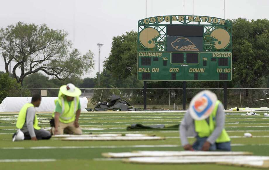 A new scoreboard stands behind workers installing the numbers June 29, 2017 in the new Robert E. Cole High School football field. Sam Houston ISD is completely rebuilding its 50-year-old field and stadium. The field, designed and produced by AstroTurf, is the first of its kind to be installed in Texas. Among other improvements the traditional rubber pellets used in most artificial turf fields are replaced with an organic product the company is calling ZeoFill that helps reduce the turf's surface temperature. Photo: William Luther / Staff Photographer / © 2017 San Antonio Express-News