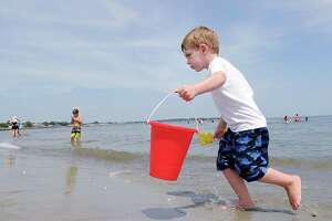 Jaxon Petrov, 3, of Greenwich, carries a bucket of water from Long Island Sound as temperatures in the low 90s brought people out to Greenwich Point in Greenwich, Conn., Friday, July 21, 2017. The National Weather Serivce is calling for a continuation of the heat wave until Sunday when the temperature will moderate in the low 80s.
