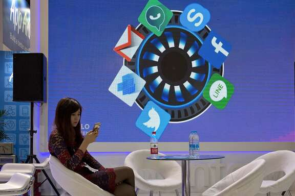 In this April 29, 2016, photo, a woman browses her smartphone near icons depicting apps that are mostly banned in China during the Global Mobile Internet Conference in Beijing. China is clamping down on use of virtual private networks, or VPNs, in a move that foreign companies worry might disrupt their operations or jeopardize trade secrets. (AP Photo/Ng Han Guan)