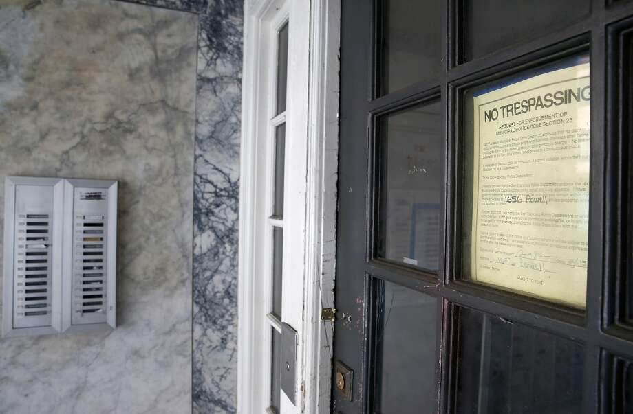 A warning notice is attached to the front door of an abandoned apartment building at Powell and Union streets in San Francisco. Photo: Paul Chinn, The Chronicle