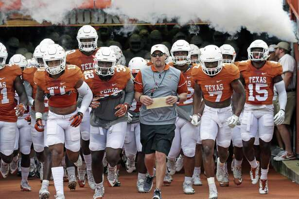 Coach Tom Herman leads his players onto the field for the Longhorns' Orange-White spring game on April 15, 2017, in Austin.
