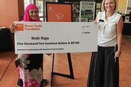 Ifra Raja, left, Klein ISD awardrecipient, receives a $1,500 scholarship check fromHeidi MacMillan, director of marketing at Houston Premium Outlets.