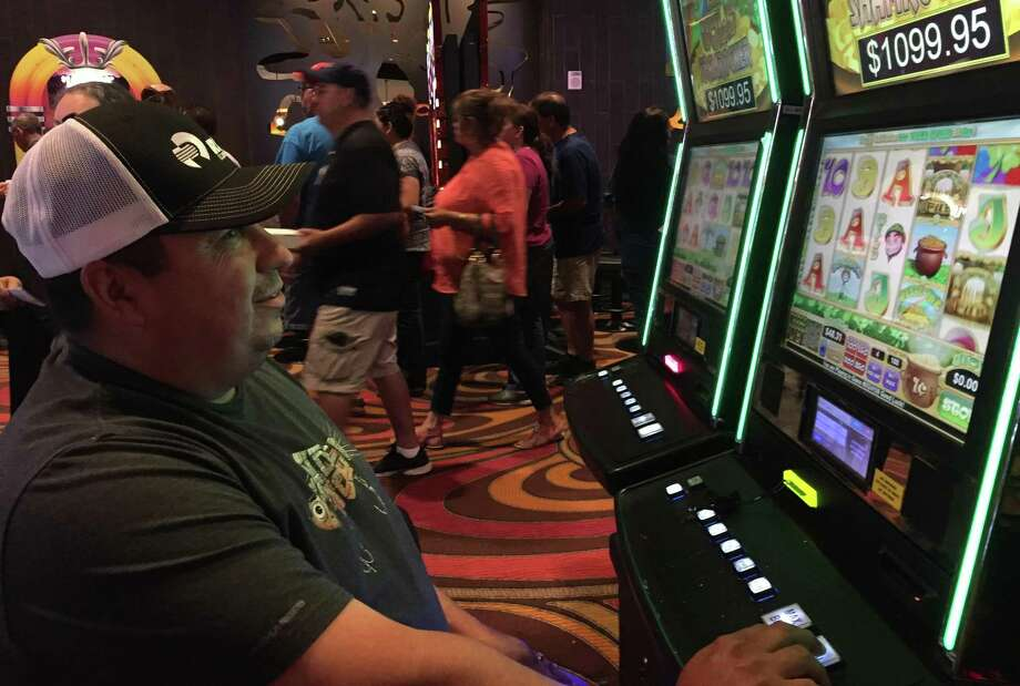 David Ytuarte, 45, of San Antonio plays a machine as other casino-goers stream by on June 11. A Harlandale High school grad, he and his wife, Janie, are frequent visitors. Photo: Diana R. Fuentes /San Antonio Express-News