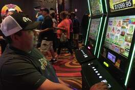 David Ytuarte, 45, of San Antonio plays a machine as other casino-goers stream by on June 11. A Harlandale High school grad, he and his wife, Janie, are frequent visitors.