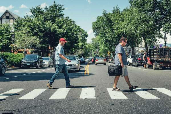 """Thrown Stone artistic directors Jonathon Winn, left, and Jason Peck cross Main Street in Ridgefield. """"Ridgefield is a place with many resources, so many performance venues. It's perfect for a mobile theater,"""" Winn says."""