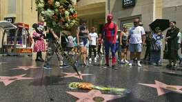 """Costumed street characters join others at a wreath in memory of actor Martin Landau at his star on the Hollywood Walk of Fame. Landaue, who won an Oscar for 's """"Ed Wood,"""" died Saturday. A reader says he is tired of """"Hollywood worship."""""""