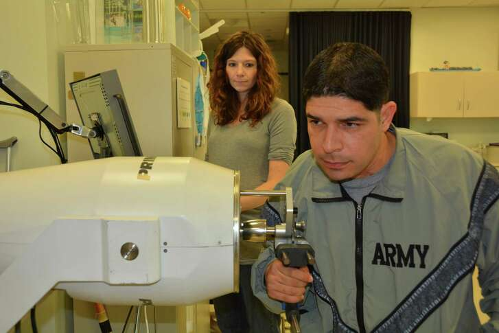 Army 1st Lt. John Arroyo works on strengthening his right hand while his occupational therapist, Katie Korp, looks on at the Center for the Intrepid in Brooke Army Medical Center's rehabilitation center at Joint Base San Antonio-Fort Sam Houston, Jan. 16, 2015. Arroyo is one of many warriors and civilians who have made tremendous strides in their recovery due to Army Medicine.