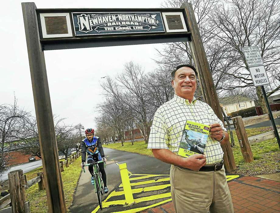 "Author Robert Madison photographed with his book, ""New Haven and Northampton Canal Greenway: Bike and Rail Trails Following the Histroric Canal"" is photographed, Thursday, January 12, 2017, at the Farmington Canal Heritage Greenway on Morse Street in Hamden. The multi-use rail trail started as a waterway, then became a railway and now spans over 80 miles through 16 towns from New Haven to Northampton, Massachusetts. (Catherine Avalone/New Haven Register) Photo: Digital First Media / Catherine Avalone/New Haven Register"