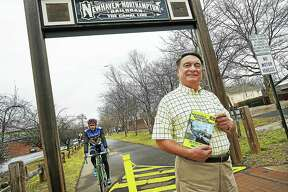 """Author Robert Madison photographed with his book, """"New Haven and Northampton Canal Greenway: Bike and Rail Trails Following the Histroric Canal"""" is photographed, Thursday, January 12, 2017, at the Farmington Canal Heritage Greenway on Morse Street in Hamden. The multi-use rail trail started as a waterway, then became a railway and now spans over 80 miles through 16 towns from New Haven to Northampton, Massachusetts. (Catherine Avalone/New Haven Register)"""