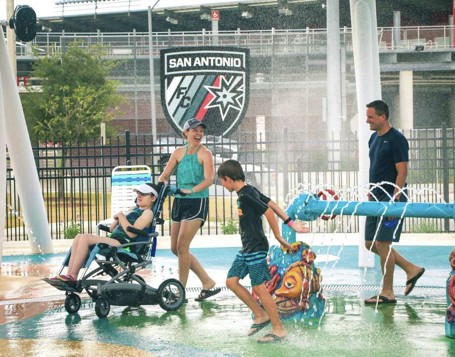 Amy and Dave Edwards of Cypress enjoy waterplay with their daughter, Claire, and son, Ryan, at Morgan's Inspiration Island in San Antonio. Photo: Joe Center
