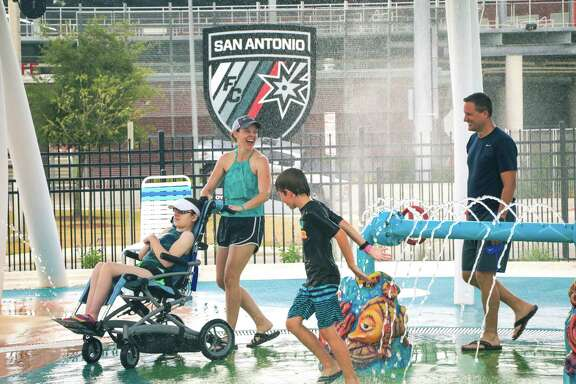Amy and Dave Edwards of Cypress enjoy waterplay with their daughter, Claire, and son, Ryan, at Morgan's Inspiration Island in San Antonio.