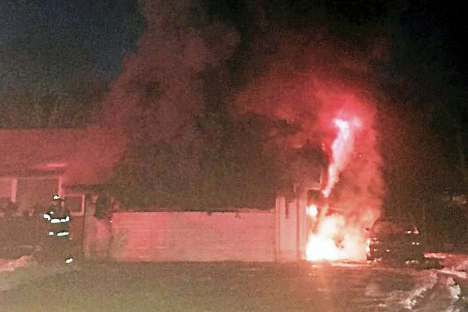 (Photo courtesy of Terrence Gould) Hamden firefighters battled a garage fire Monday night at 6 Wilson Lane, just off Benham Street. The flames were contained to the garage but the home sustained heat and smoke damage. Photo: Digital First Media