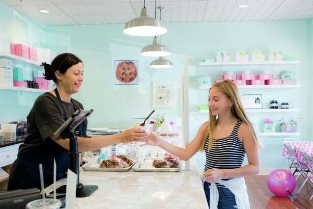 Andrea Greene serves Addie Strouse, 13, of Trumbull, a helping of edible raw cookie dough at Connecticut Cookie Company in Fairfield.