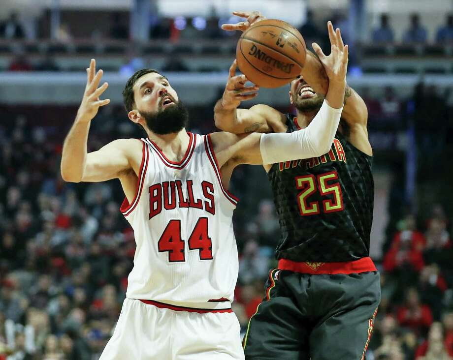 FILE - In this Wednesday, Jan. 25, 2017, file photo, Chicago Bulls forward Nikola Mirotic (44) fouls Atlanta Hawks forward Thabo Sefolosha (25) during the first half of an NBA basketball game in Chicago. Teams, and the league, try to make the transition to the NBA easier for all players, but internationals need some special attention. Mirotic said international players, even those from different countries, tend to stick together on the road. They go to movies and dinners together because they often have similar interests. (AP Photo/Kamil Krzaczynski, File) Photo: AP / FR136454 AP