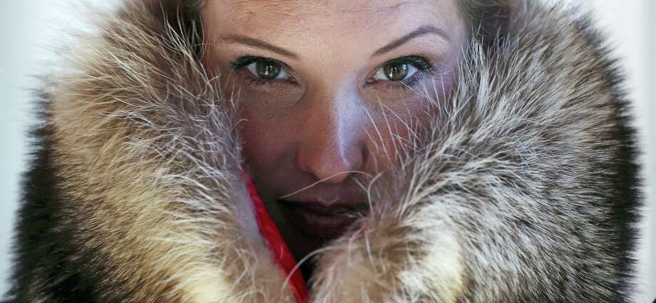 """Pamela Paquin poses with an """"accidental fur"""" raccoon neck muff she created. Photo: AP / AP"""