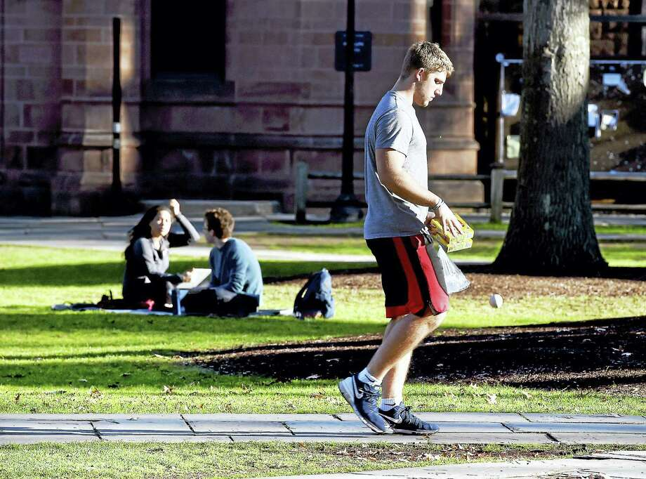 (Arnold Gold-New Haven Register)  Yale freshman Quintin Herbert walks through Yale University's Old Campus in New Haven during finals week on 12/15/2015.  Herbert is from Cincinnati, Ohio, where the weather has been just as warm. Photo: Journal Register Co.