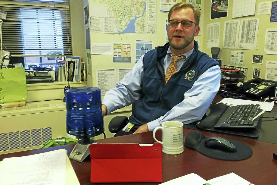 New Haven Transportation, Traffic and Parking Director Doug  Hausladen displays a blue light on his desk on Wednesday, Dec. 30, at 200 Orange St. The lights are slated to be installed at sites around the city to notify motorists of parking bans. Esteban L. Hernandez New Haven Register Photo: Journal Register Co.
