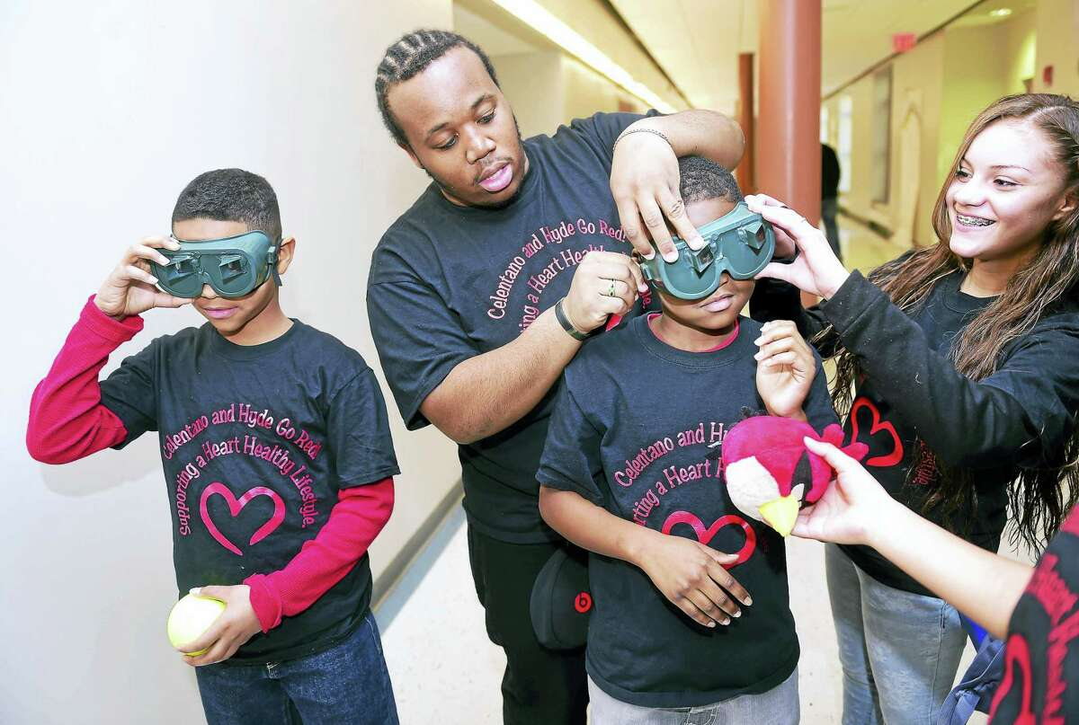 (Arnold Gold-New Haven Register) Tyrese Coardes (center) and Jeramie Guzman (right) of The Hyde School of Health Sciences and Sports Medicine adjust goggles on Trevon Green, during the second annual Go Red for a Healthy Heart event at Celentano Biotech Health and Medical Magnet School in New Haven on 2/26/2016. The goggles altered the wearers perspective by thirty degrees. Green and Naszar Hobby (left), 11, were tasked with throwing an object to a partner with the goal of having their eyes compensate for the altered perspective.